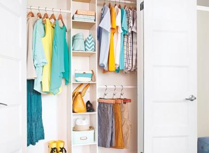 Garde-robe blanche remplie de vêtements sur plusieurs espaces de rangements. Vêtements féminins et masculins de couleur pastel.