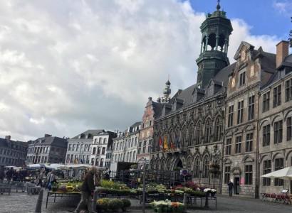 La photo montre la Grand Place de Mons, occupée par des petits commerçants. On remarque l'Hôtel de Ville à droite de la photo.