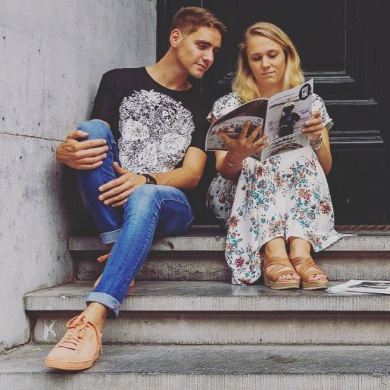 Une fille et un garçon assis sur les marches de l'université en train de lire un magazine P'Tit Torê