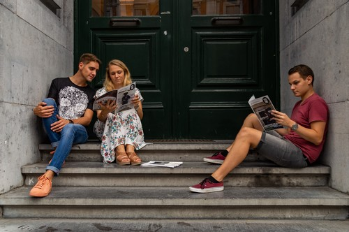 Une fille et deux garçons assis sur les marches de l'université en train de lire un magazine P'Tit Torê